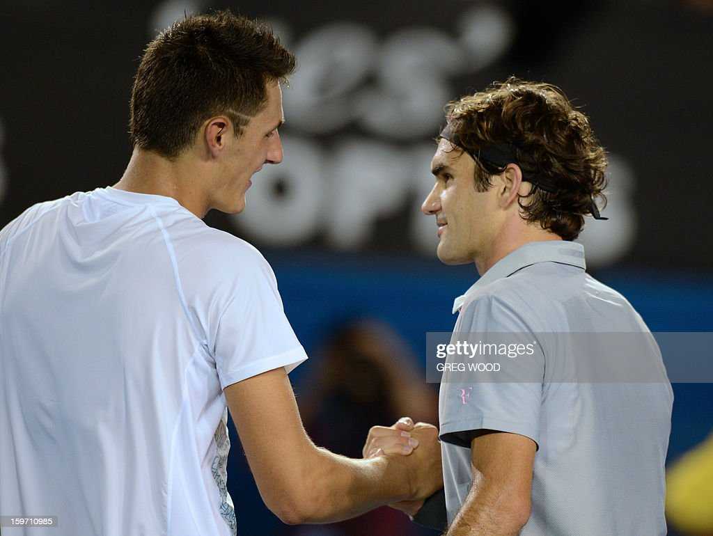 Switzerland's Roger Federer (R) shakes hands after victory in his men's singles match against Australia's Bernard Tomic on the sixth day of the Australian Open tennis tournament in Melbourne on January 19, 2013.