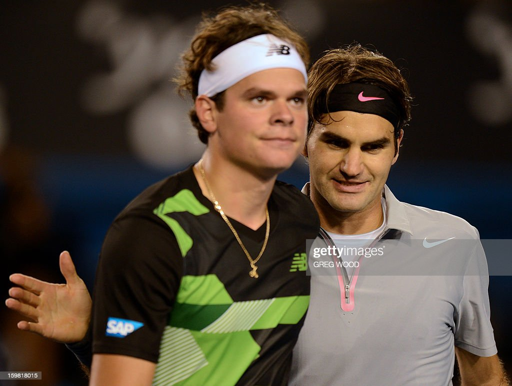 Switzerland's Roger Federer (R) shakes hands after victory in his men's singles match against Canada's Milos Raonic on the eighth day of the Australian Open tennis tournament in Melbourne on January 21, 2013.