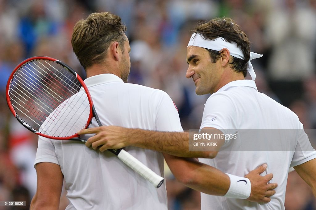 Switzerland's Roger Federer (R) shakes hands and ebraces Britain's Marcus Willis (L) at the net after Federer won their men's singles second round match on the third day of the 2016 Wimbledon Championships at The All England Lawn Tennis Club in Wimbledon, southwest London, on June 29, 2016. / AFP / GLYN