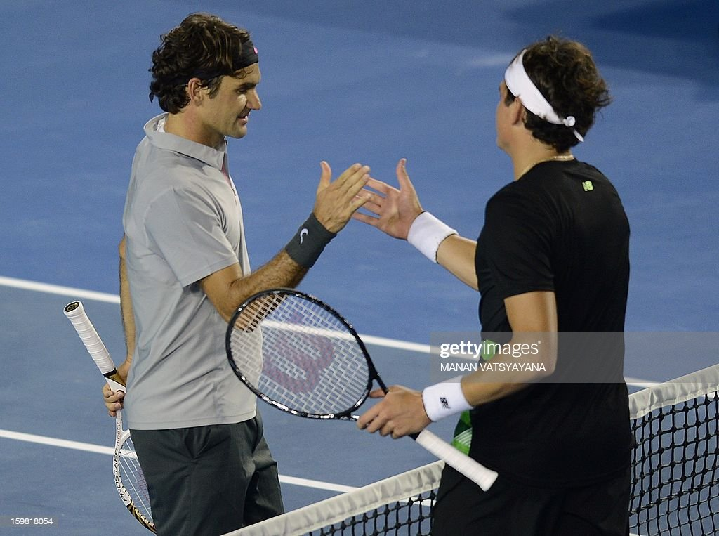 Switzerland's Roger Federer (L) shakes hands with Canada's Milos Raonic after his victory during their men's singles match on day eight of the Australian Open tennis tournament in Melbourne on January 21, 2013.