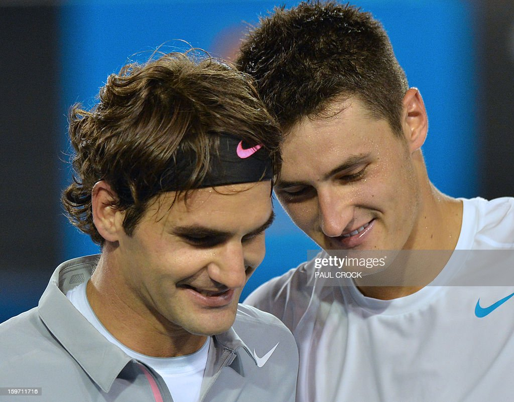 Switzerland's Roger Federer (L) shares a light moment after victory in his men's singles match against Australia's Bernard Tomic (R) on the sixth day of the Australian Open tennis tournament in Melbourne on January 19, 2013. AFP PHOTO/PAUL CROCK IMAGE STRICTLY RESTRICTED TO EDITORIAL USE - STRICTLY NO COMMERCIAL USE