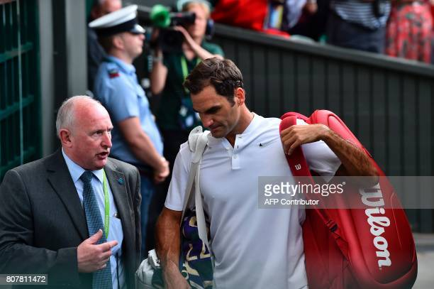 Switzerland's Roger Federer talks with an official as he leaves the court after his opponent Ukraine's Alexandr Dolgopolov retired during their men's...