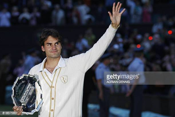 Switzerland's Roger Federer waves holding his trophy after being defeated by Spain's Rafael Nadal during their final tennis match of the 2008...