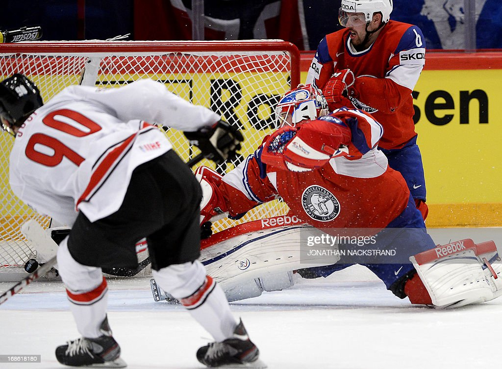 Switzerland's Roman Josi (L) shoots to score on Norway's goalkeeper Lars Haugen during the preliminary round match Norway vs Switzerland at the 2013 IIHF Ice Hockey World Championships on May 12, 2013 in Stockholm.