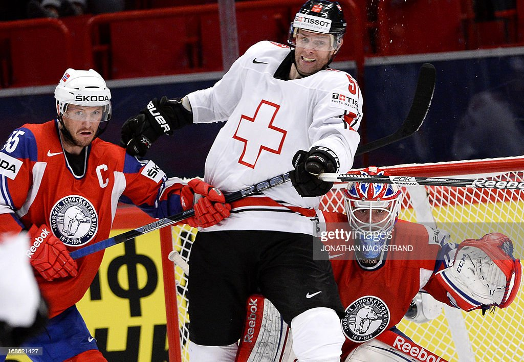 Switzerland's Ryan Gardner (C) vies with Norway's Ole-Kristian Tollefsen and goalkeeper Lars Haugen during the preliminary round match Norway vs Switzerland at the 2013 IIHF Ice Hockey World Championships on May 12, 2013 in Stockholm. AFP PHOTO/JONATHAN NACKSTRAND