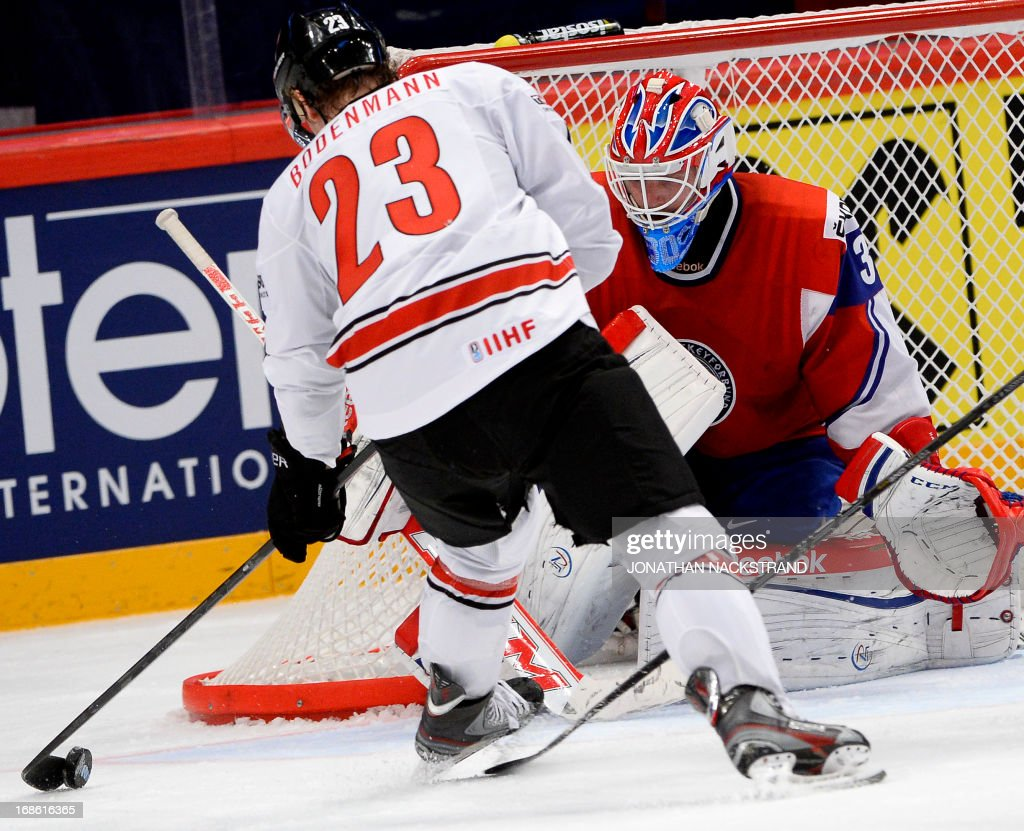 Switzerland's Simon Bodenmann (L) tries to score on Norway's goalkeeper Lars Haugen during the preliminary round match Norway vs Switzerland at the 2013 IIHF Ice Hockey World Championships on May 12, 2013 in Stockholm.