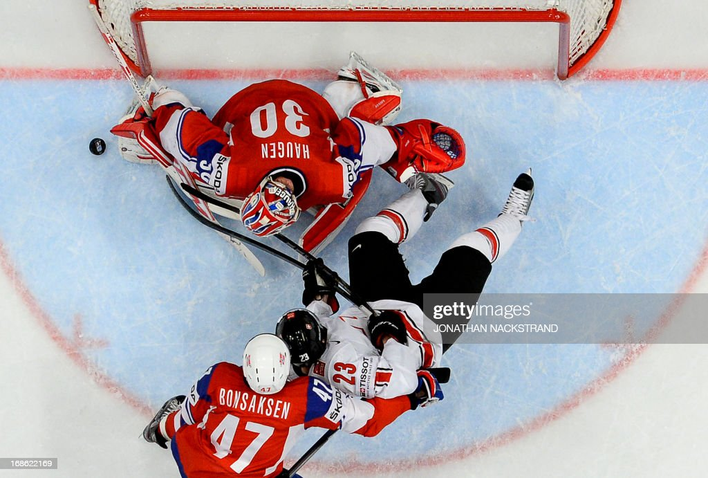 Switzerland's Simon Bodenmann (C) tries to score on Norway's goalkeeper Lars Haugen during the preliminary round match Norway vs Switzerland at the 2013 IIHF Ice Hockey World Championships on May 12, 2013 in Stockholm. Switzerland won 3-1
