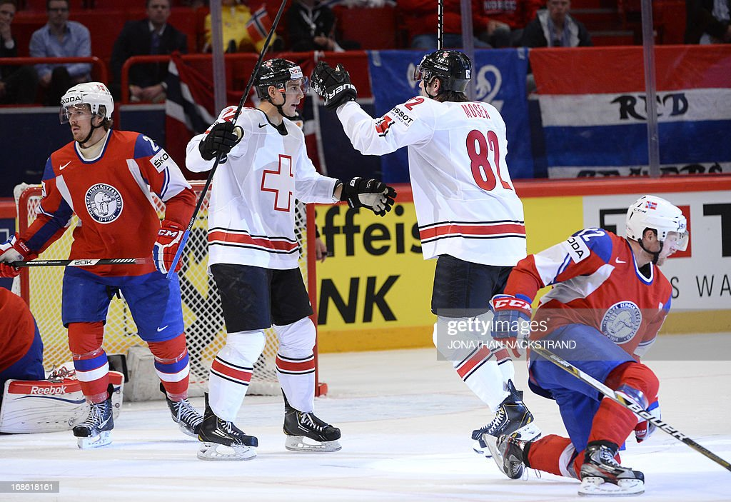 Switzerland's Simon Moser (2nd-R) celebrates with a teammate after scoring during the preliminary round match Norway vs Switzerland at the 2013 IIHF Ice Hockey World Championships on May 12, 2013 in Stockholm.