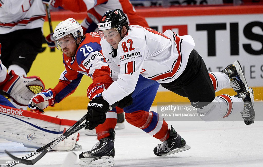 Switzerland's Simon Moser (R) falls as he shoots to score on Norway's goalkeeper Lars Haugen during the preliminary round match Norway vs Switzerland at the 2013 IIHF Ice Hockey World Championships on May 12, 2013 in Stockholm.