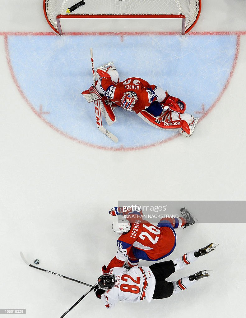 Switzerland's Simon Moser falls as he shoots to score on Norway's goalkeeper Lars Haugen during the preliminary round match Norway vs Switzerland at the 2013 IIHF Ice Hockey World Championships on May 12, 2013 in Stockholm.