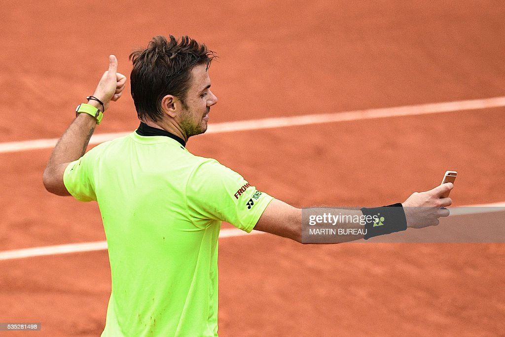 Switzerland's Stanislas Wawrinka poses for a selfie after winning his men's fourth round match against Serbia's Victor Troicki at the Roland Garros 2016 French Tennis Open in Paris on May 29, 2016. / AFP / MARTIN