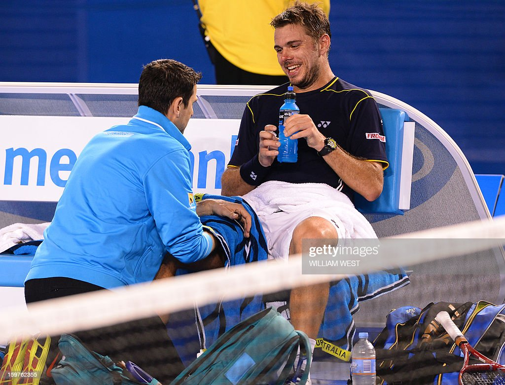 Switzerland's Stanislas Wawrinka receives treatment during a break in his men's singles match against Serbia's Novak Djokovic on the seventh day of the Australian Open tennis tournament in Melbourne on January 20, 2013.