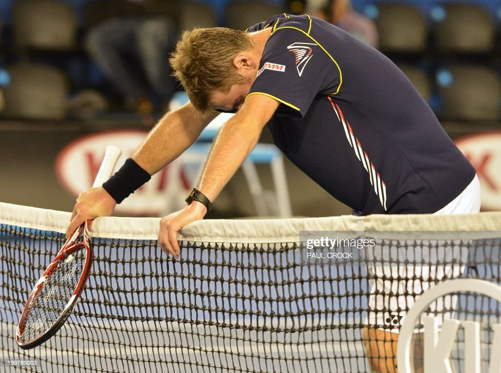 Switzerland's Stanislas Wawrinka rests on the net following his defeat to Serbia's Novak Djokovic during their men's singles match on day seven of the Australian Open tennis tournament in Melbourne early on January 21, 2013.