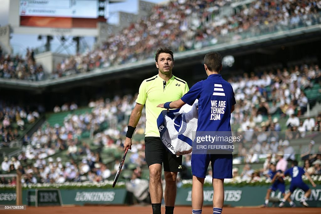 Switzerland's Stanislas Wawrinka takes a towel from a ball boy during his men's third round match against France's Jeremy Chardy at the Roland Garros 2016 French Tennis Open in Paris on May 27, 2016. / AFP / Eric FEFERBERG