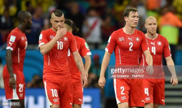 Switzerland's Stephan Lichtsteiner and Switzerland's Granit Xhaka look dejected after the final whistle