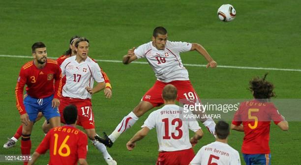 Switzerland's striker Eren Derdiyok jumps to head the ball during the 2010 World Cup group H first round football match between Spain and Switzerland...
