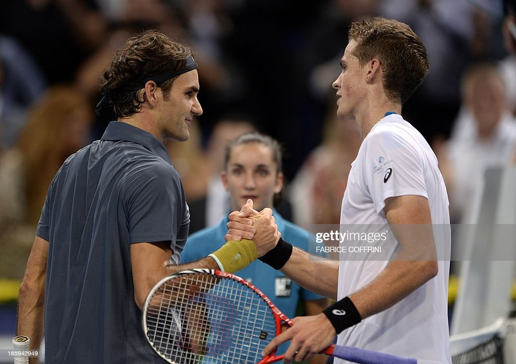 Switzerland's tennis player Roger Federer (L) shakes hands with Canada's Vasek Pospisil after Federer won their semi-final tennis match at the Swiss Indoors ATP tournament in Basel on October 26, 2013.