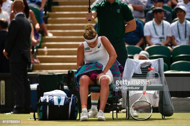 Switzerland's Timea Bacsinszky touches her bandaged leg as she sits in the break between games against Poland's Agnieszka Radwanska during their...