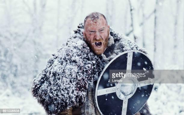 Schwert schwingende blutigen Wikinger Krieger versteckt hinter seinem Schild in einem Schneesturm winter