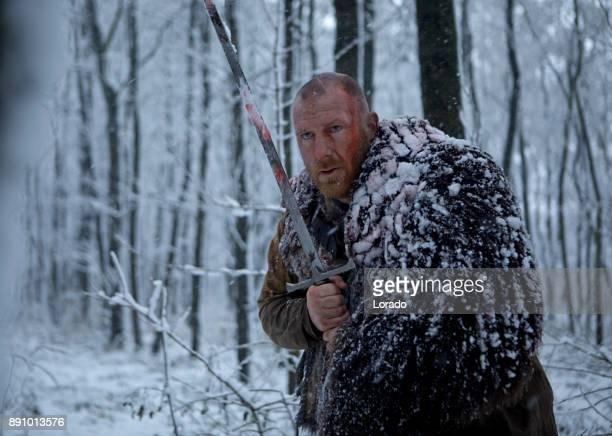 Schwert schwingende blutigen Wikinger-Krieger in einem Schneesturm Winterwald