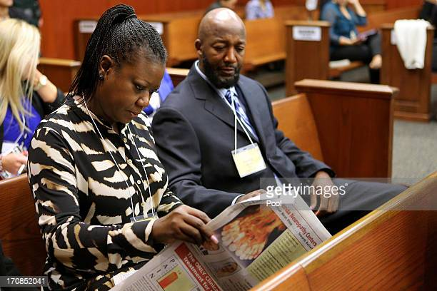 Sybrina Fulton and Tracy Martin the parents of slain teen Trayvon Martin read the Orlando Sentinel as they wait for the start of the eighth day of...