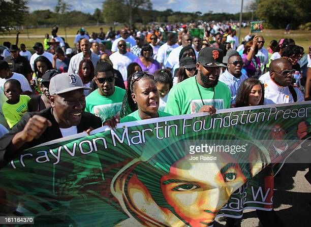 Sybrina Fulton and Tracy Martin walk with supporters during the 'March for Peace' at Ives Estate Park in honor of their late son Trayvon Martin on...