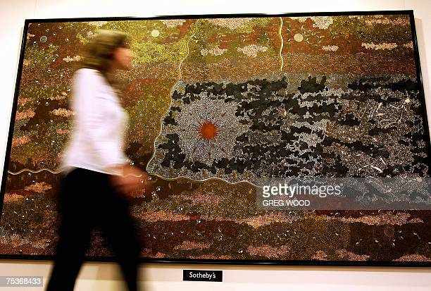 A Sotheby's employee walks past a painting by Aboriginal artist Clifford Possum Tjapaltjarri titled 'Warlugulong 1977' in Sydney 12 July 2007...