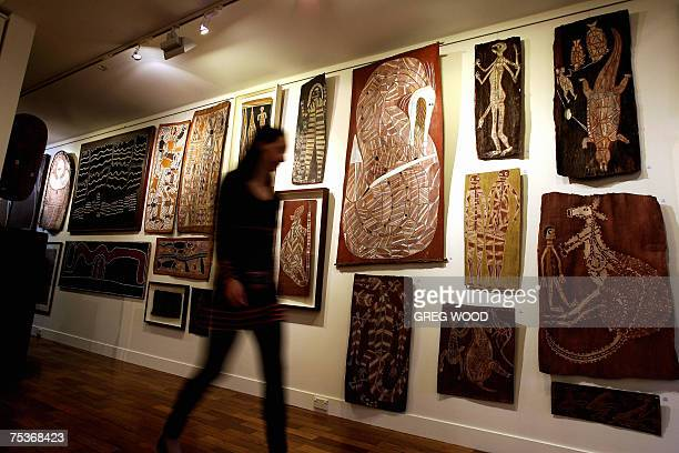 A Sotheby's employee walks past Aboriginal artwork in Sydney 12 July 2007 A painting by Clifford Possum Tjapaltjarri titled 'Warlugulong 1977' along...
