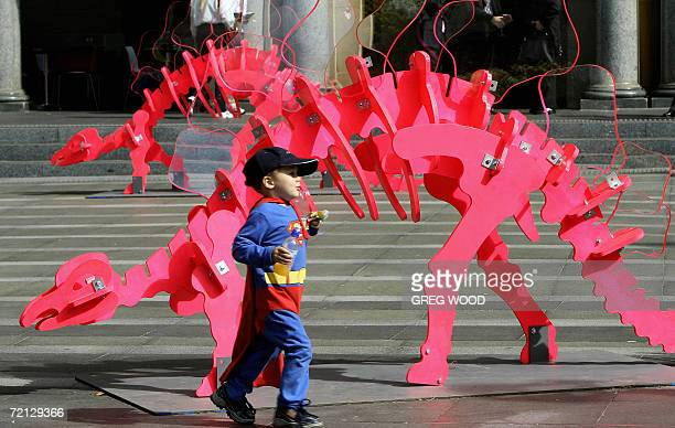 A young boy dressed as Superman runs past a large scale dinosaur sculpture on Sydney's Customs House forecourt 10 October 2006 The artwork titled...