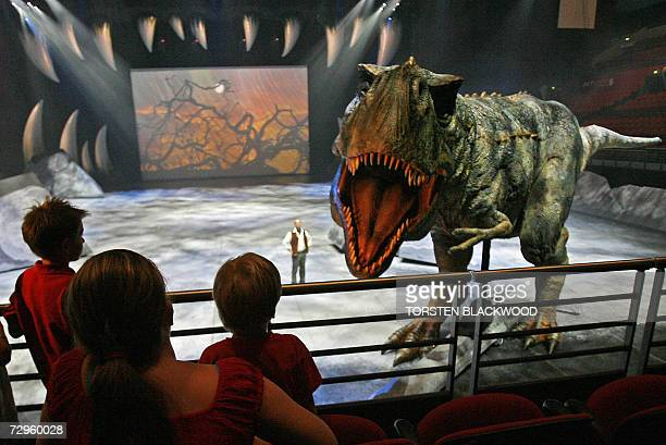 Children watch an automated Tyrannosaurus Rex during the world preview of the 'Walking With Dinosaurs The Live Experience' show in Sydney 10 January...