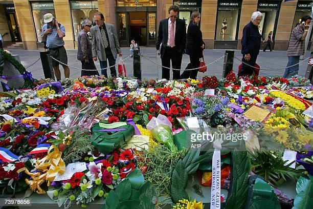 Passerbys look at messages of remembrance bouquets of flowers photographs of family members at the Cenotaph in Sydney's Martin Place the day after...