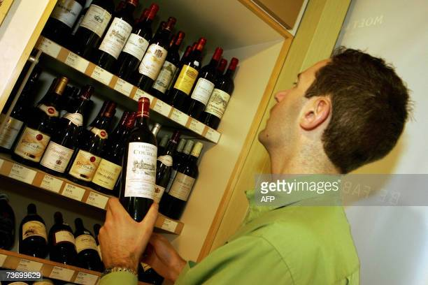 TO GO WITH AustraliaFrancewineschedFEATURE A man reaches for a bottle of Bordeaux wine from the shelves at the local liquor shop in Sydney 22 March...