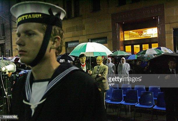 Two Australian war veterans Sir Brian Dudley and Ronald Rayman stand in the rain at a dawn ANZAC Day service in the Cenotaph in Sydney's Martin Place...