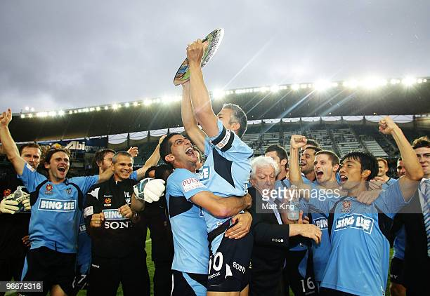 Sydney captain Steve Corica holds aloft the minor premiership trophy and celebrates with Simon Colosimo after the round 27 ALeague match between...