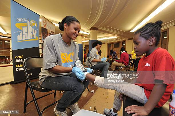Sydney Carter of the Chicago Sky fits a child recipient with a new pair of shoes during the Samaritan Feet Shoe Distribution on May 11 2012 at...