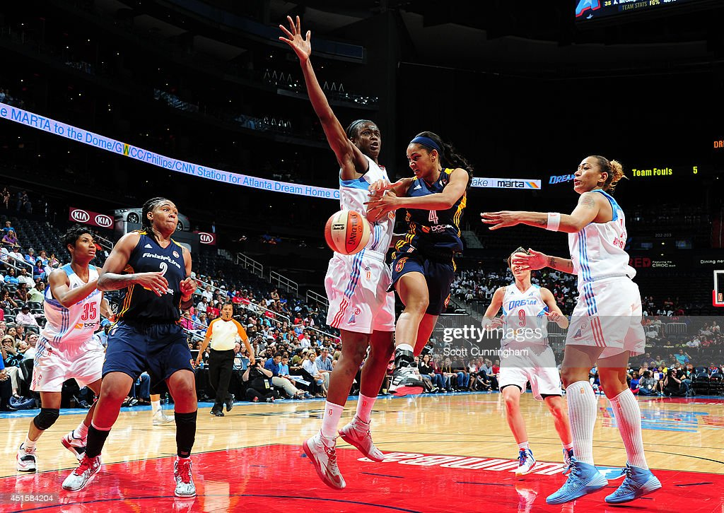 Sydney Carter #4 of the Indiana Fever passes off against Aneika Henry #13 of the Atlanta Dream on July 1, 2014 at Philips Arena in Atlanta, Georgia.