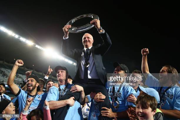 Sydney FC coach Graham Arnold is hoisted up by players with the ALeague trophy in front of fans following the 2017 ALeague Grand Final match between...