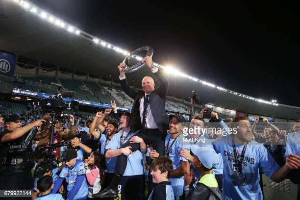 Sydney FC coach Graham Arnold is lifted by players and holds aloft the ALeague trophy in front of The Cove after the 2017 ALeague Grand Final match...