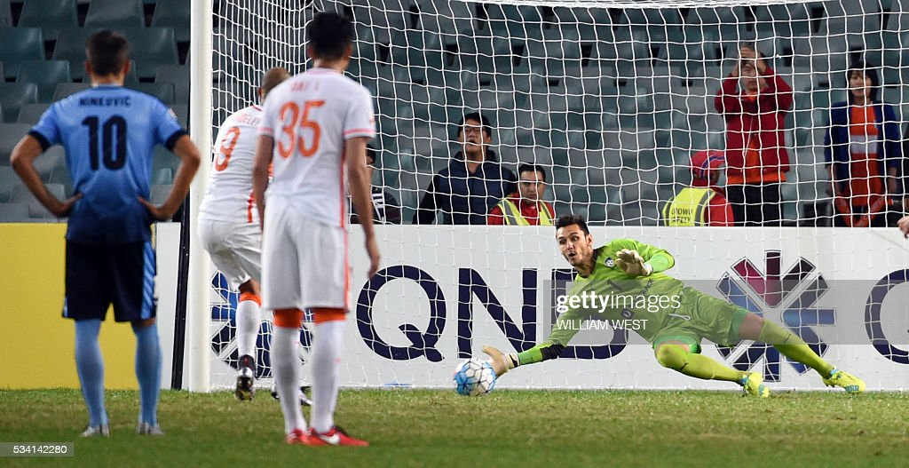 Sydney FC goalkeeper Vedran Janjetovic (R) saves a penalty taken by Shandong Luneng player Diego Tardelli Martins (2/L) during their AFC Champions League round of 16 second leg football match in Sydney on May 25, 2016. / AFP / WILLIAM