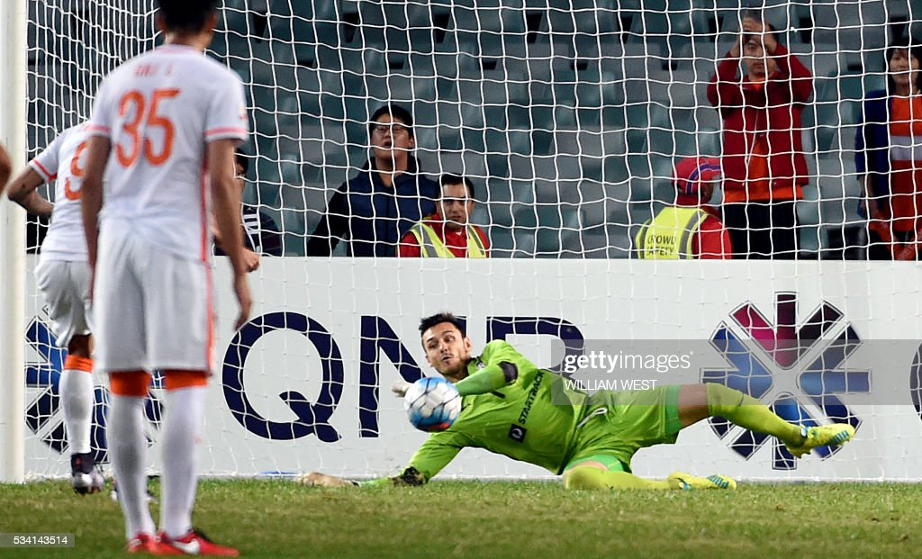 Sydney FC goalkeeper Vedran Janjetovic (R) saves a penalty taken by Shandong Luneng player Diego Tardelli Martins (L) during their AFC Champions League round of 16 second leg football match in Sydney on May 25, 2016. / AFP / WILLIAM