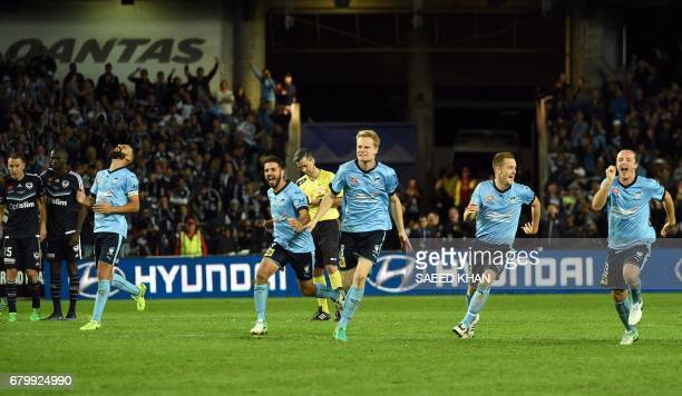 Sydney FC players react after winning the penalty shootout to win the 2017 ALeague Grand Final football match against Melbourne Victory at Allianz...