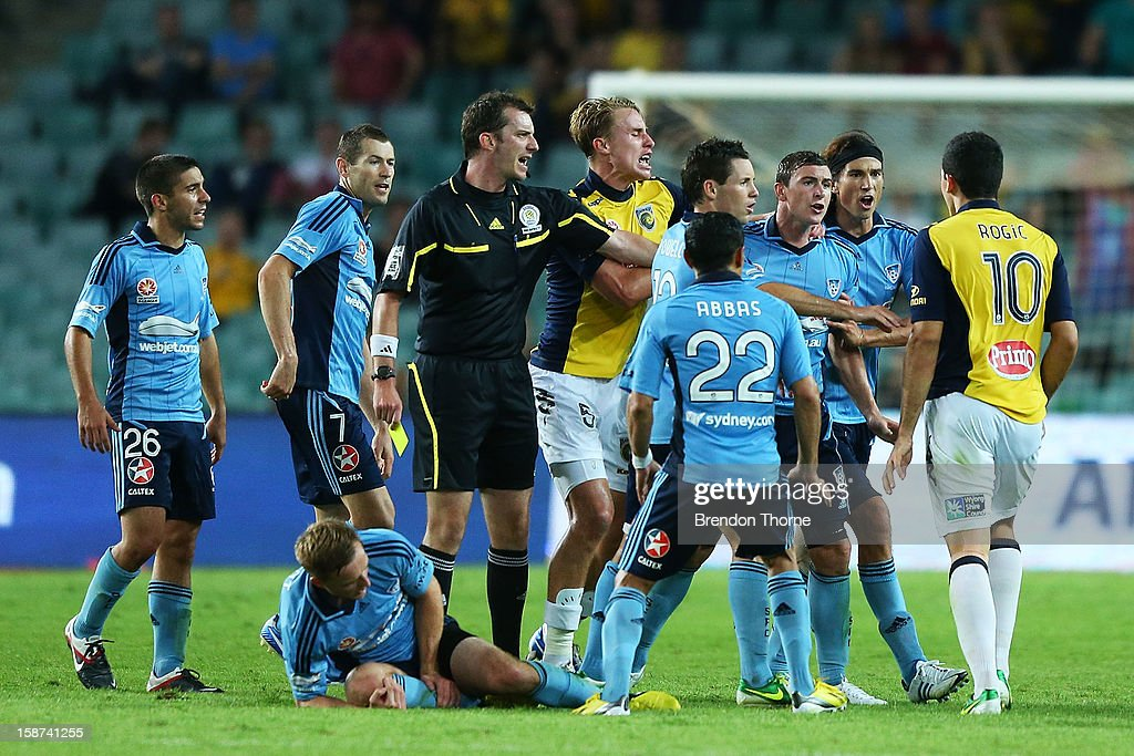 Sydney FC players react strongly towards Tom Rogic of the Mariners after fouling Rhyan Grant of Sydney during the round 13 A-League match between Sydney FC and the Central Coast Mariners at Allianz Stadium on December 27, 2012 in Sydney, Australia.