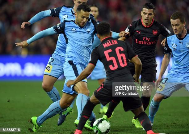 Sydney FC's player BOBO fights for the ball with Arsenal's player Donyell Malen during their football friendly match in Sydney on July 13 2017 / AFP...