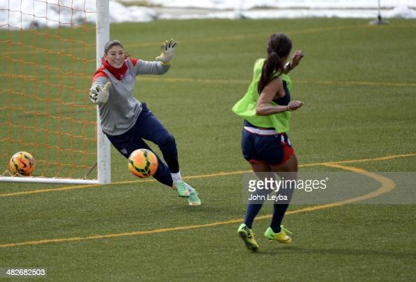 Sydney Leroux FW with the USA women's soccer team takes a shot on goal as GK Hope Solo makes the attempt to save it during their practice April 3...