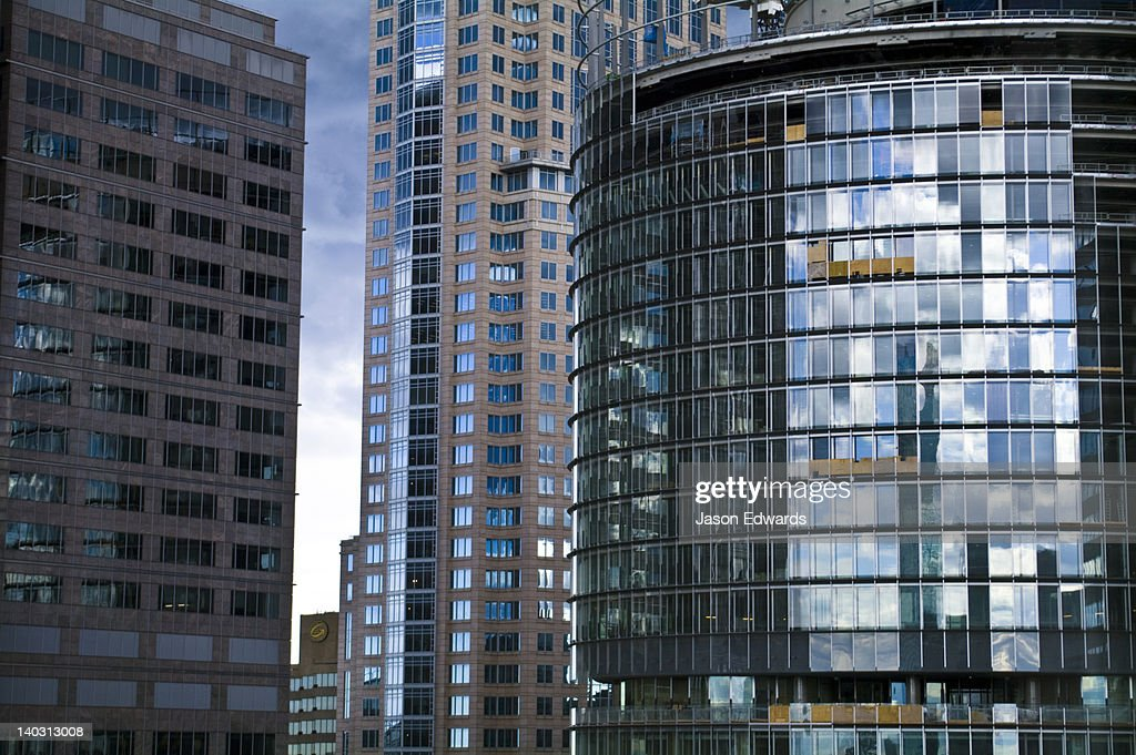 Grey storm clouds reflected in the glass of a circular office tower. : ストックフォト