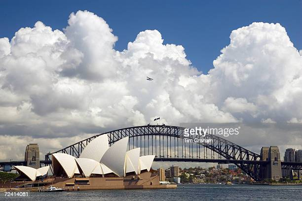 Sydney Opera House and Sydney Harbour Bridge with small plane flying over Australia