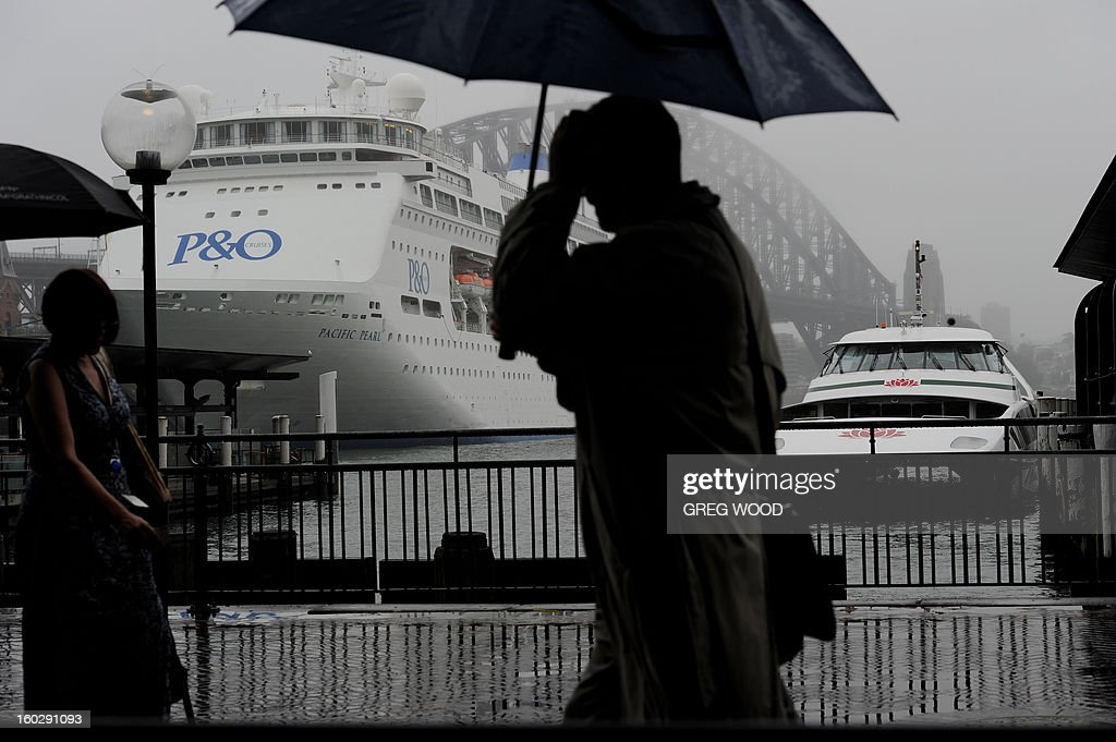 Sydney residents shelter under umbrellas as early morning rain falls while walking along Circular Quay on Sydney Harbour on January 29, 2013. Ex-tropical cyclone Oswald has been causing flooding down Australia's east coast, but predicted heavy rain and damaging wind warnings have been cancelled for Sydney, AFP PHOTO / Greg WOOD
