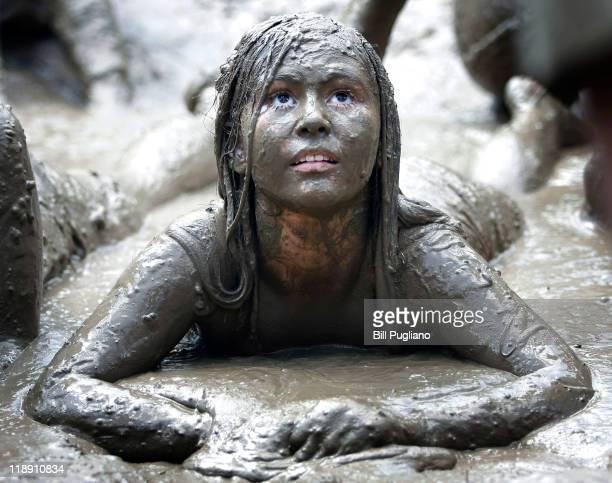 Sydney Truba of Melvindale Michigan lies in a giant lake of mud during Wayne County's 2011 Mud Day event at Nankin Mills Park July 12 2011 in...
