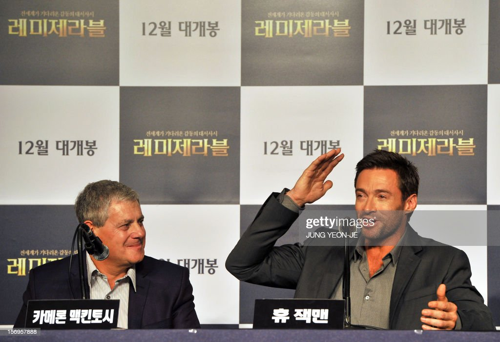 Sydney-born Hollywood star actor Hugh Jackman (R) gestures as producer Cameron Mackintosh (L) looks on during a press conference to promote their film 'Les Miserables' at a hotel in Seoul on November 26, 2012. The film will open in December in South Korea. AFP PHOTO / JUNG YEON-JE