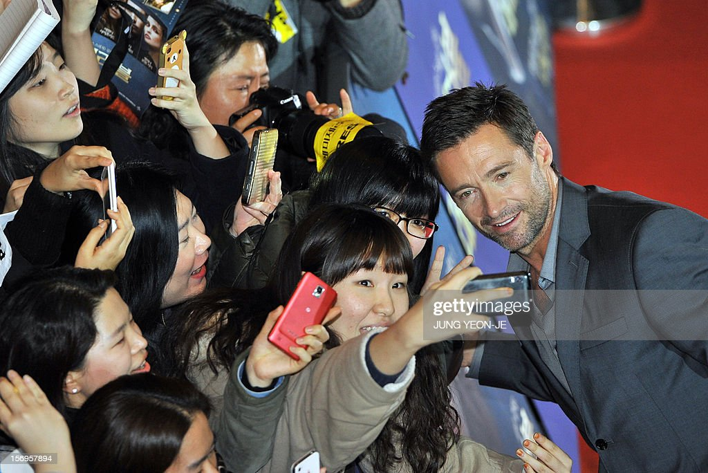 Sydney-born Hollywood star actor Hugh Jackman (R) poses with South Korean fans for a photo after a press conference to promote his film 'Les Miserables' at a hotel in Seoul on November 26, 2012. The film will open in December in South Korea.